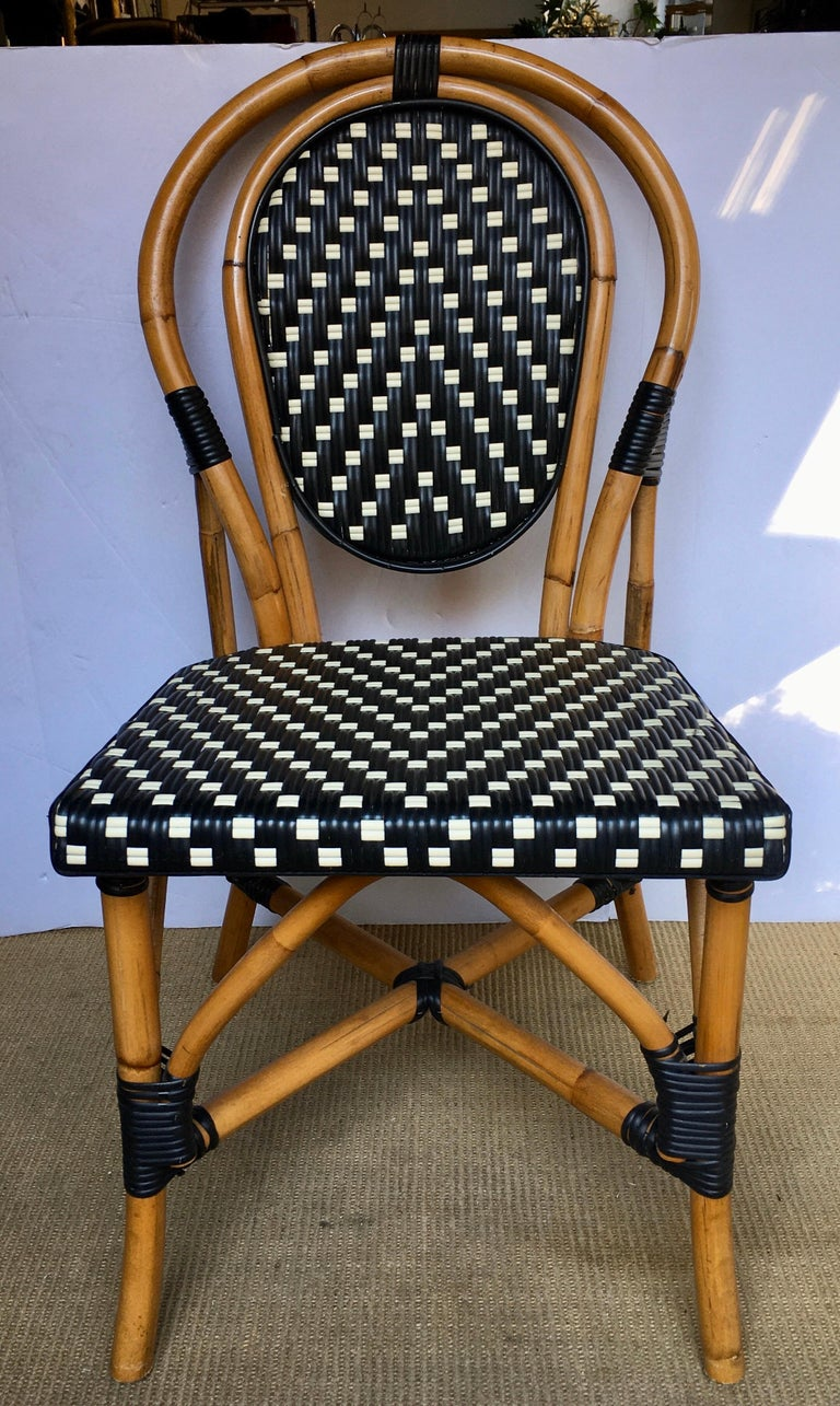 Classic French style bistro dining side chair just like those you find in a Paris café. Frame expertly handcrafted of natural Malacca/Manau steamed bent cane with neutral black/ivory woven nylon seat and back. For indoor and outdoor use under