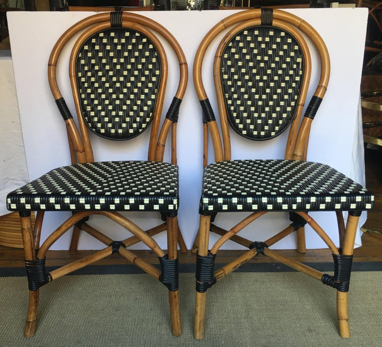 Set of four Classic French style bistro dining side chairs just like those you find in a Paris café. Frames expertly handcrafted of natural Malacca/Manau steamed bent cane with neutral black/ivory woven nylon seats and backs. For indoor and outdoor