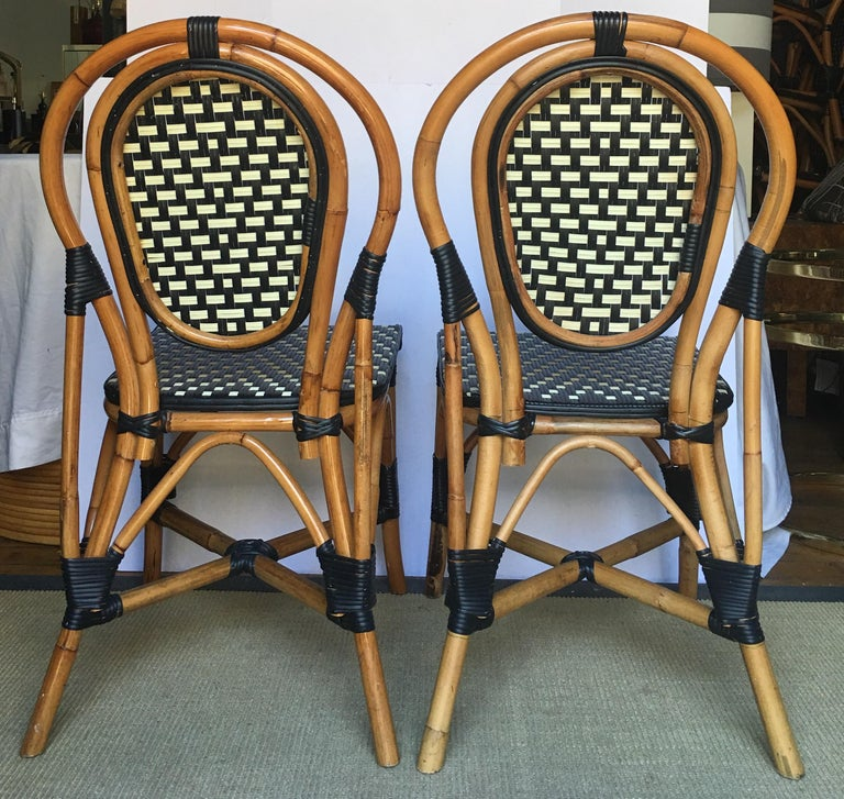 Pair of Classic French style bistro dining side chairs just like those you find in a Paris café. Frames expertly handcrafted of natural Malacca/Manau steamed bent cane with neutral black/ivory woven nylon seats and backs. For indoor and outdoor use