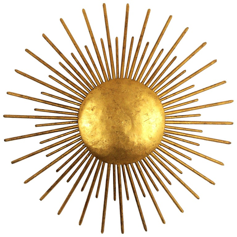 Art Decohand-hammered iron gold leaf gilt sunburst flush mount, France, 1940s A hand-hammered gilt iron sunburst ceiling light fixture or wall sconce with gold leaf finish and Art Deco accents in transition to Brutalist style.  A highly