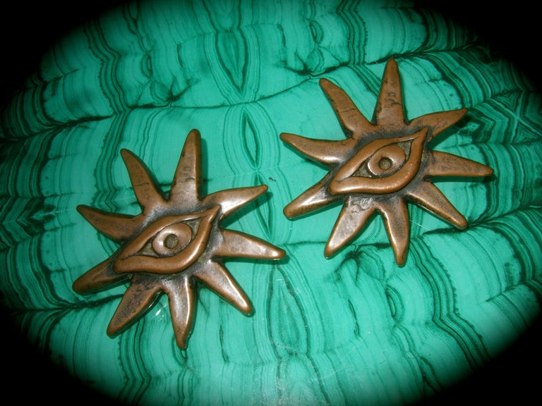 French surrealist bronze metal sunburst eye themed clip-on earrings designed by Scooter Paris  The unique figural large-scale earrings are designed with radiating beams with an eye  placed in the center   They make a very bold, avant-garde accessory