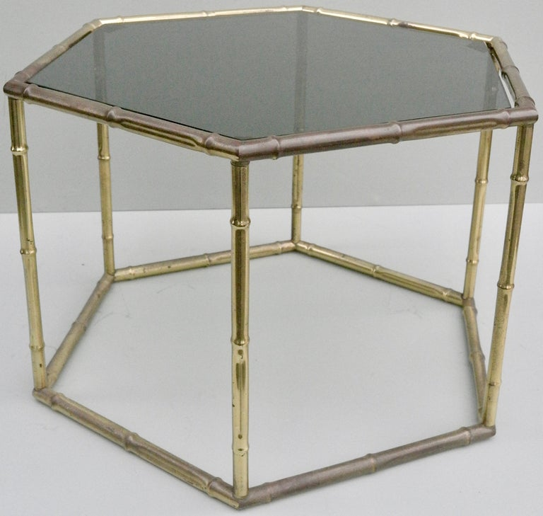 French symmetrical gold metal bamboo side table with dark glass top.