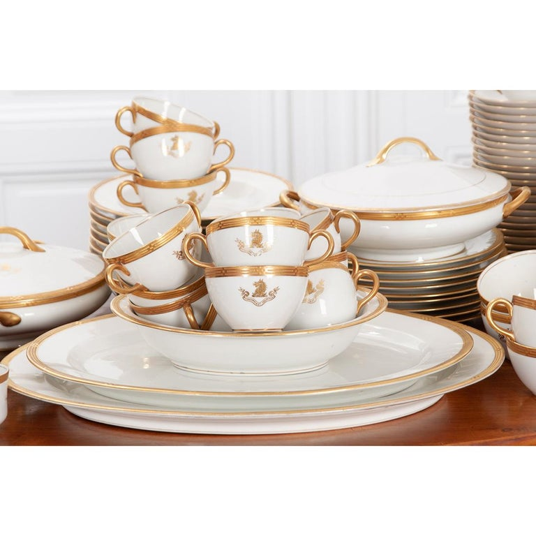 """This fine, O.P. Co. Syracuse porcelain 132-piece service has the Dent family coat of arms as part of the gilt design on most of the pieces along with a unique gilt banding on all the pieces.  This service consists of:  11 dinner plates – 1"""""""