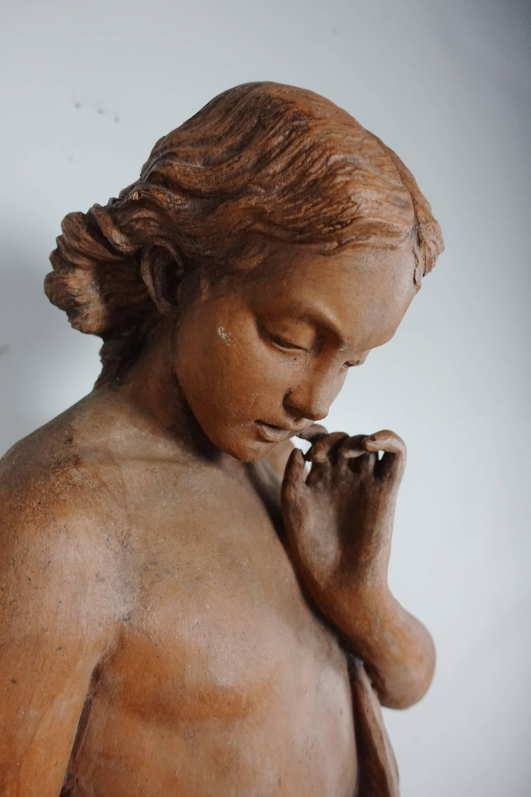 1930s French terracotta figure of a woman holding a flower. She is mounted on an iron base.