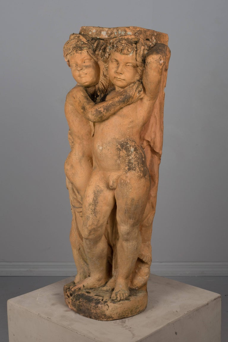 An early 20th century French terracotta garden statue of two embracing cherubs. In excellent condition with old surface moss. Weight: 120 lbs. Most garden sculptures are stored outside where it continues to acquire additional lichen and moss. Please