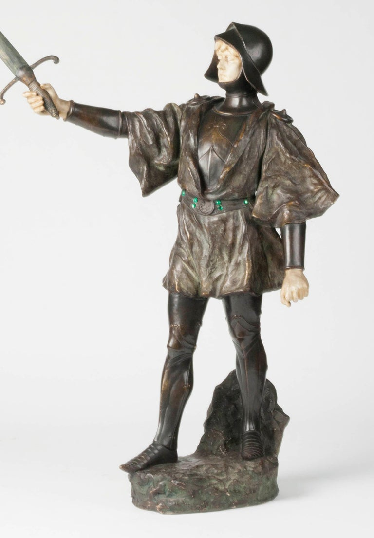 Beautiful terracotta statue of a knight with a sword. The image is signed J. Dupré. The image also has a blind mark that says 'Reproduction Reservée', which can be translated as 'All rights reserved'. The image has a beautiful, powerful appearance.