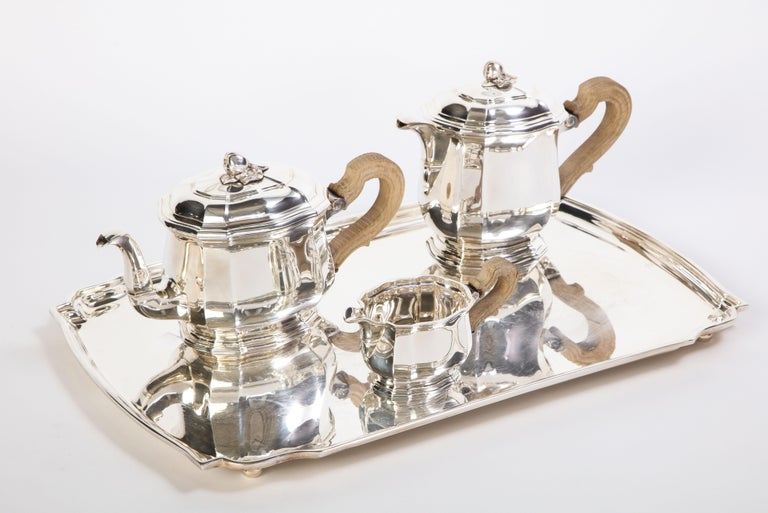 A French sterling silver and carved wood three-piece tea and coffee service, retailed by Tiffany & Co., New York, circa 1990. Comprising: a teapot, a coffee pot, and a creamer. The underside of teapot engraved: