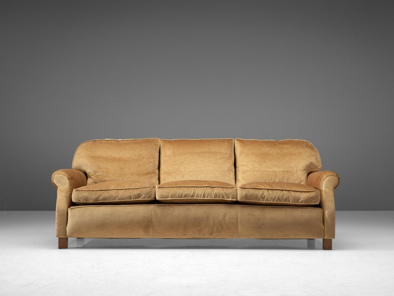Three-seat sofa, velvet and wood, France, 1940s.  Grand and comfortable three-seat sofa in beige velvet upholstery. Very comfortable sofa that features a deep and thick seat with thick cushions. The armrests are curved and give the sofa and more