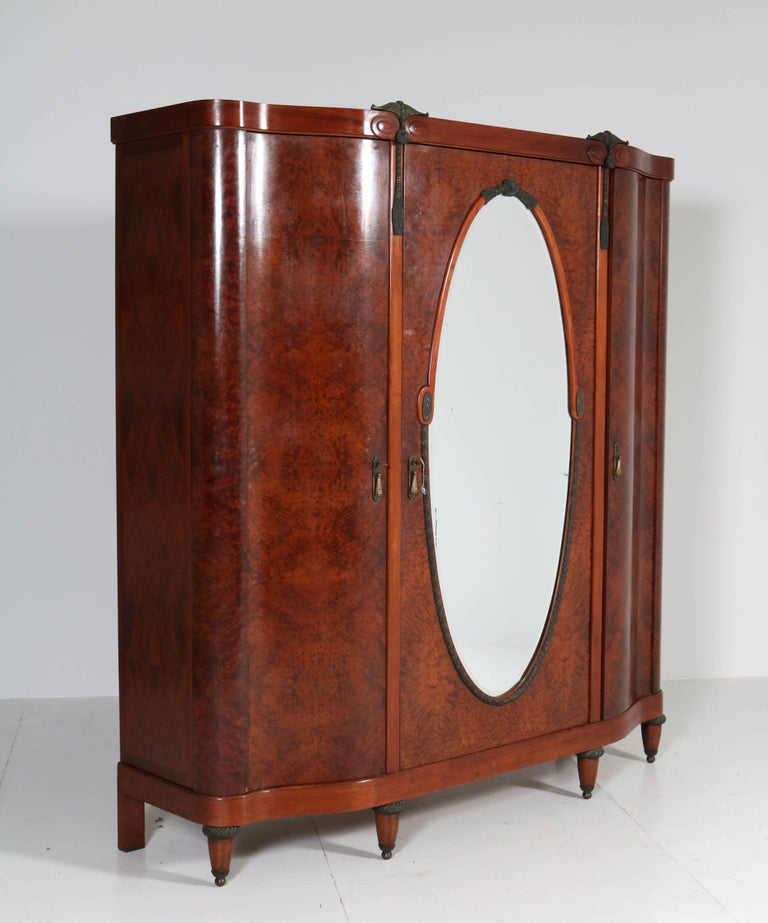 Stunning and rare Art Deco wardrobe or armoire. Striking French design from the thirties. Thuya burl with original bronze handles and ornaments. Behind the door with the original beveled mirror is a brass bar for hanging clothes. Eight wooden