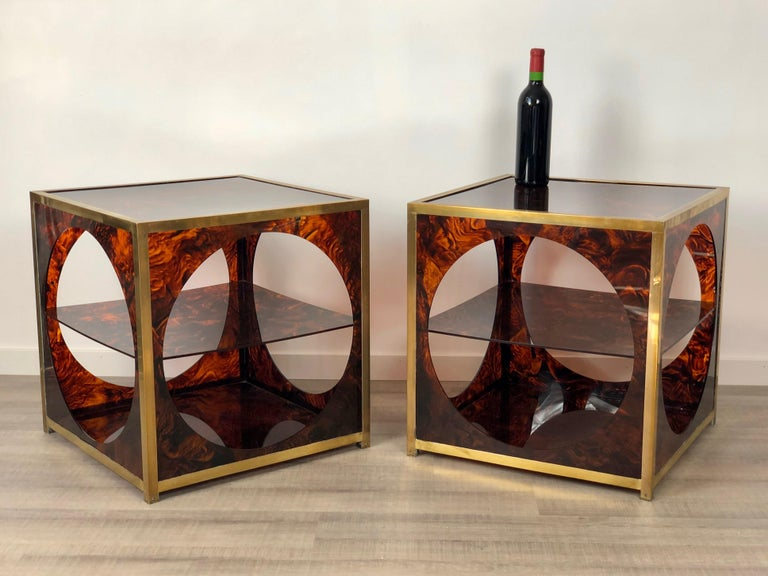 Pair of elegant side/coffee tables in faux tortoiseshell lucite and brass details. They feature an unique geometrical design that remembers 1970s' Christian Dior style: an open cube with circular windows inside which a Lucite shelf is
