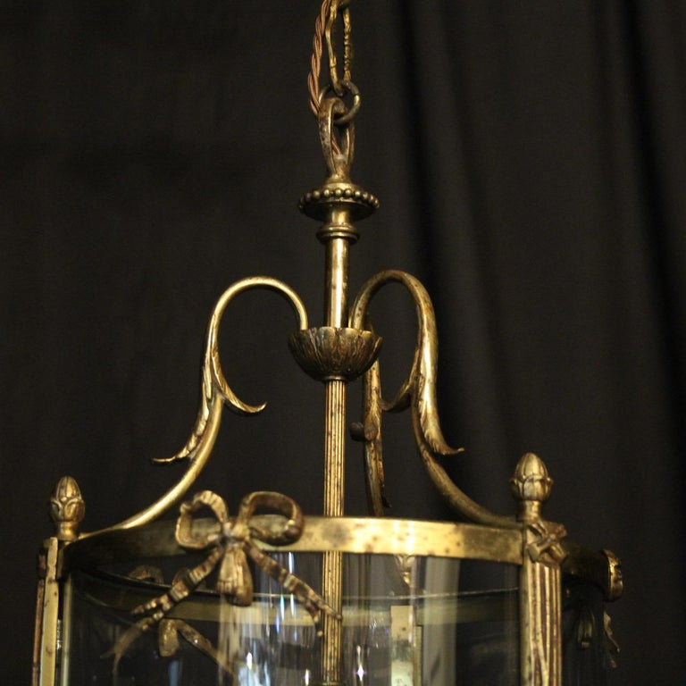 A French gilded cast bronze triple light antique hall lantern, the three scrolling light fittings surrounded by three sectional convex glass panels and held within an ornate scrolling framework with leaf side sections, pierced ribbon embellishments,