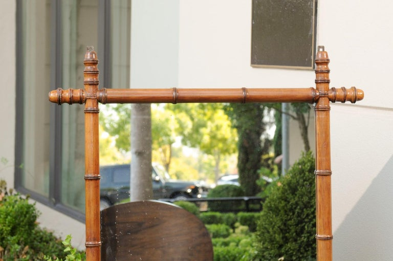 A French rustic faux-bamboo walnut mirror from the early 20th century, with brown patina and turned protruding corners. Born in France at the turn of the century, this charming mirror features a rectangular silhouette presenting a thin brown faux