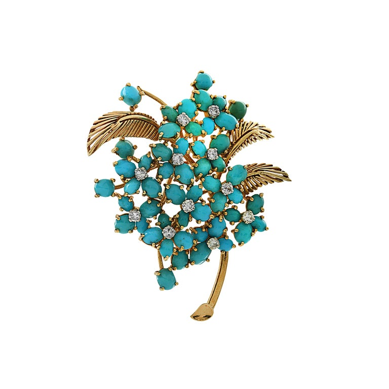 Ornate French brooch pin crafted in 18 karat yellow gold, featuring turquoise cabochons arranged in flower clusters, detailed with 11 round brilliant cut diamonds weighing approximately .35 carats total, G color, VS-SI clarity.  This delightful