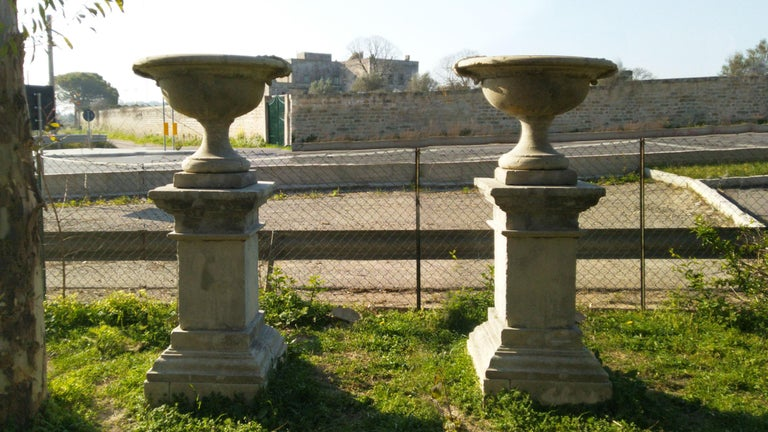 A massive pair of French urns with pedestals, in solid limestone hand-carved, very large and tall. Acanthus leaves handcrafted as well on sides. More info on demand.