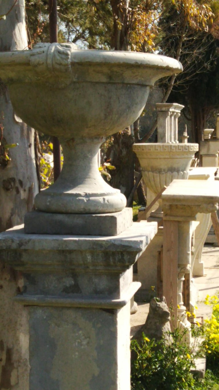 French Urns with Pedestals 'Pair' Hand-carved in Pure Limestone, antique finish. In Good Condition For Sale In LOS ANGELES, CA