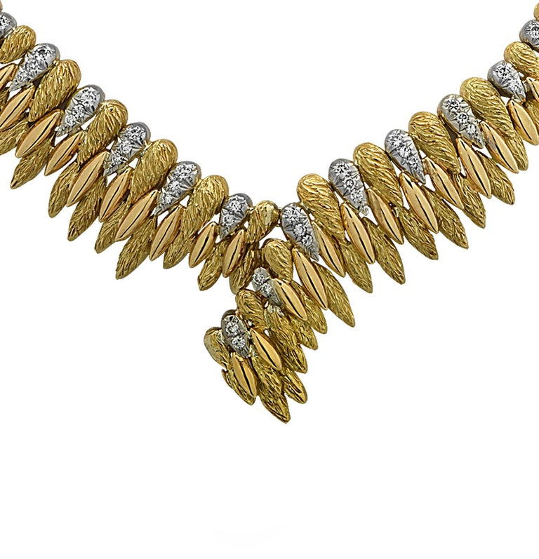 Finely crafted in France, this stunning 18 karat white and yellow gold v-shaped necklace features 54 round brilliant cut diamonds weighing approximately 1.35 carats total, G color, VS-SI clarity. Textured yellow gold beads, highly polished yellow