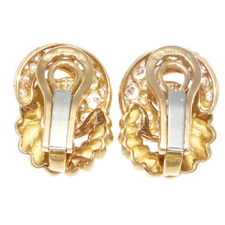 Elegant and classic double hoop earrings by Verdura featuring one twisted gold hoop and one diamond encrusted hoop. With 2.50 carats total weight in diamonds, graded D-E color, VS clarity. Stamped with French eagle head. Each earring is .5 inches