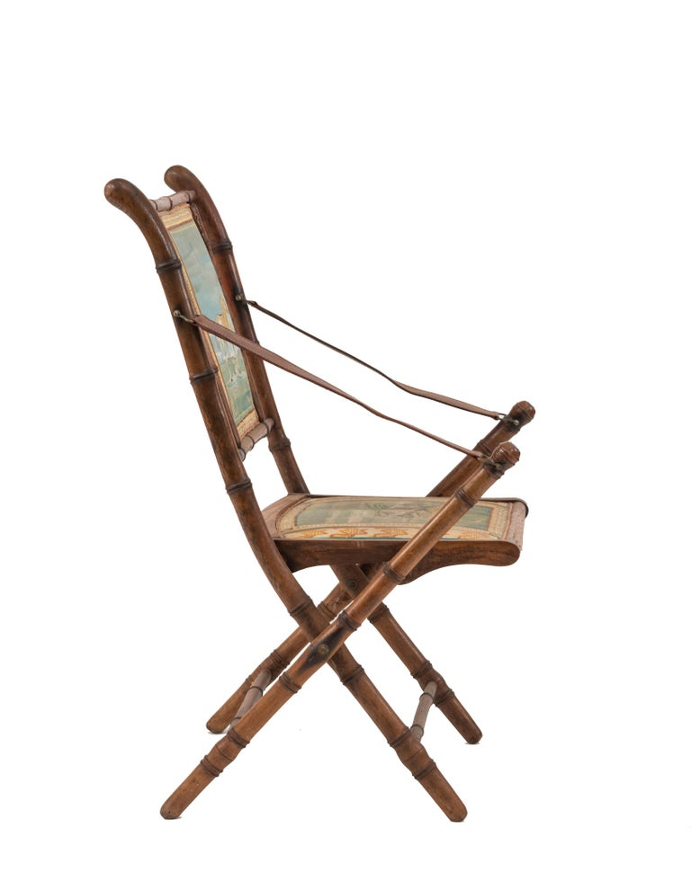 French Victorian oak faux bamboo Campaign design folding armchairhaving modern painted seat and back panels with animals and leather arm straps.