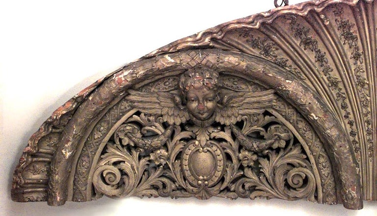French Victorian large gilt arch shaped horizontal wall plaque with 3 carved winged cupid heads and scroll filigree design.