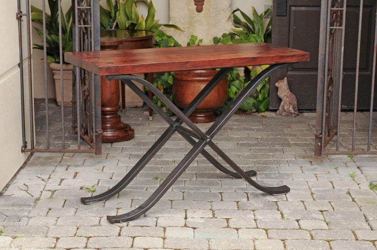 A vintage French narrow walnut and iron table from the mid-20th century, with curving x-form base. Born in France during the mid-century period, this stylish table features a rectangular planked walnut top accented with large nailheads, sitting