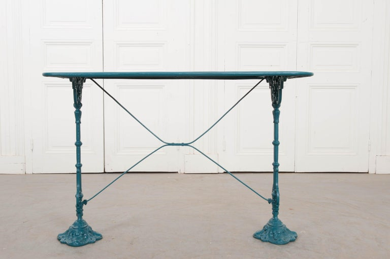A charming vintage painted cast-iron and sheet metal bistro table, circa 1910, from France. The rectangular sheet-metal surface rests on two notched cast-iron legs stabilized by an X-form stretcher above stylized diamond-shaped feet. It has recently
