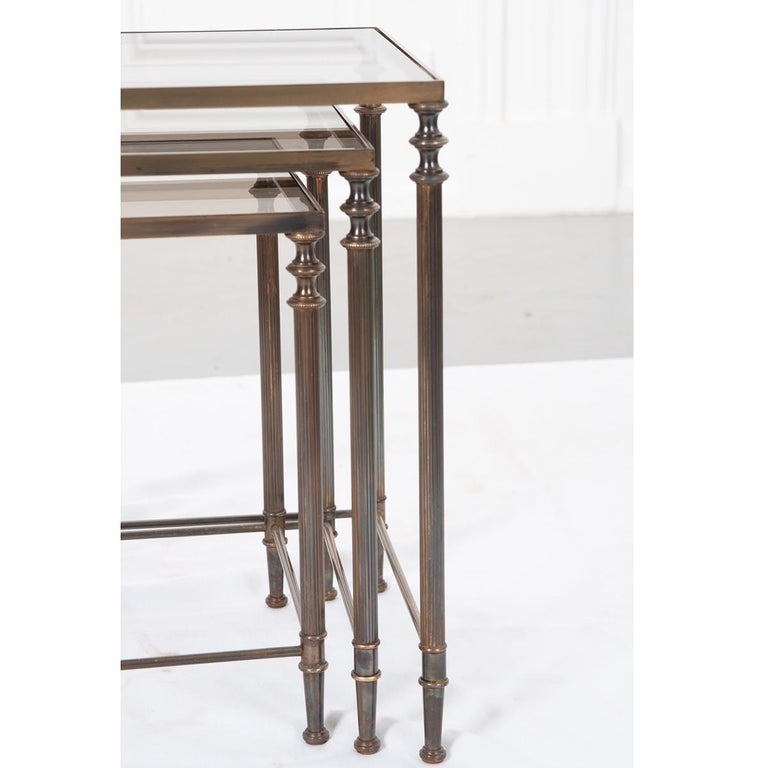 """Set of three French, brass nesting tables with inset tinted glass tops. The four legs have turned-like caps with fluted columns and turned-like feet. Simple brass rod stretchers connect the legs for an added detail.   Dimensions: 1. 17-¼""""H x 20-⅞""""W"""