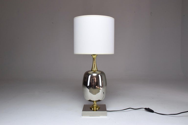 A 20th-century French vintage table statement lamp fully restored in nickel-plated brass, gold polished brass details, and new cylinder fabric shade. The main part of the lamp was originally brass plated which we stripped of to reveal the silver.