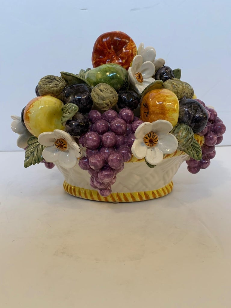 A beautiful Majolica style ceramic bowl of fruit and flowers from France having incredible coloration and detail. Says fait main and made in France on the bottom.