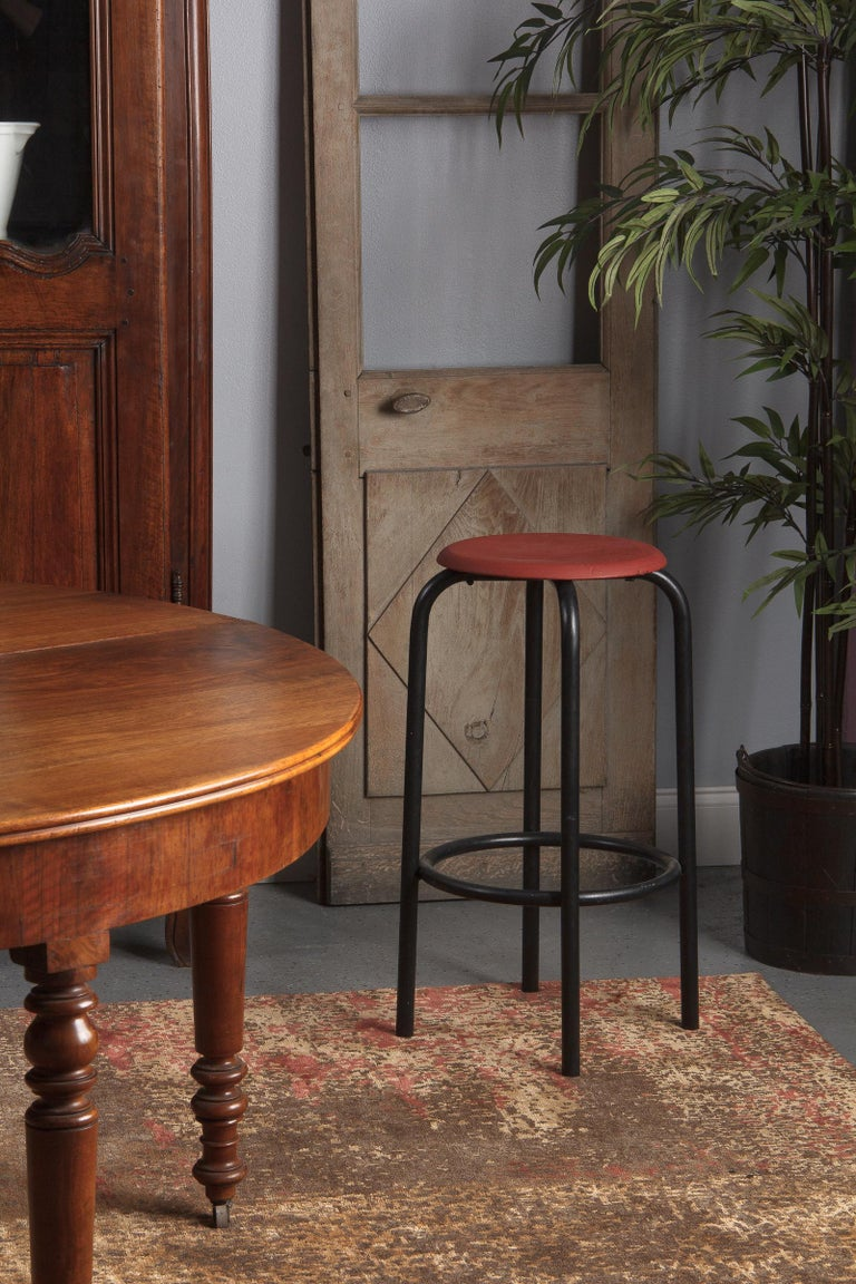 A midcentury French Industrial stool with tubular metal legs painted black and a round pine seat painted red. The seat is 12.5