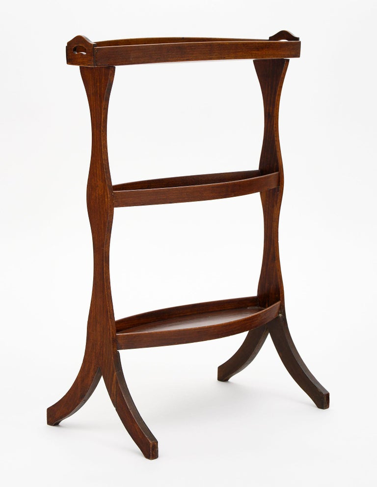 French vintage walnut side tables from the Art Deco period. These solid walnut and burled walnut tables have side legs with a flair out at the base. There are three levels on each; and the top features handles to easily move the tables for