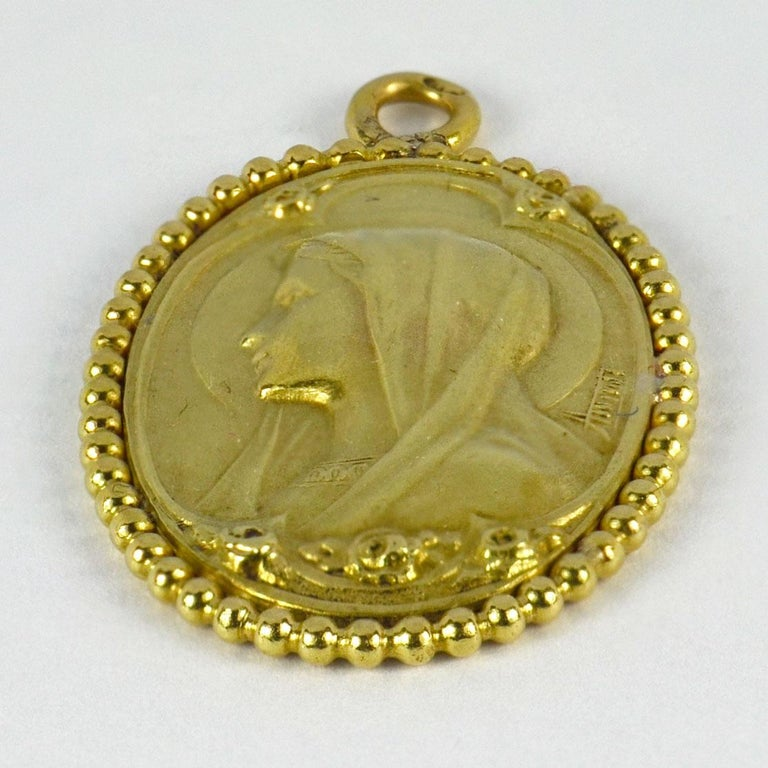 An 18 karat (18K) yellow gold pendant designed as a medal depicting the Virgin Mary with a beaded surround. Engraved to the reverse with a monogram of MT/MF and the date '25 Avril 1926' with roses and a sunburst.  Stamped with the eagle's head for