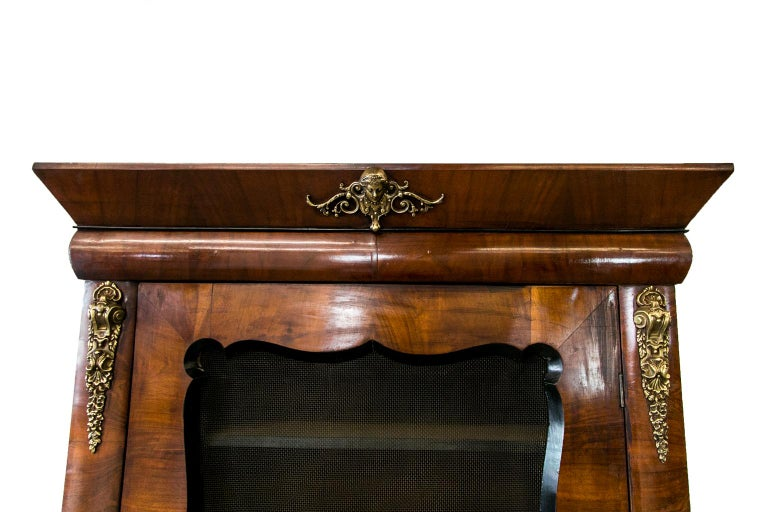 This French walnut bookcase has a wire mesh door with beveled ebonized scalloped framing. The stiles and frieze have convex banding in heavy cast brass ornamentation, four interior shelves. The stiles terminate in ebonized scroll feet. It has the