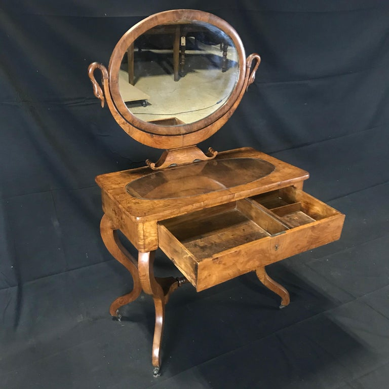 Beautiful French dressing table with mirror in carved walnut with elegant swan neck support uprights. On the sides the mirror is supported by two arms carved in the wood in the shape of a swan. Under the mirror a handy drawer for storing toiletries