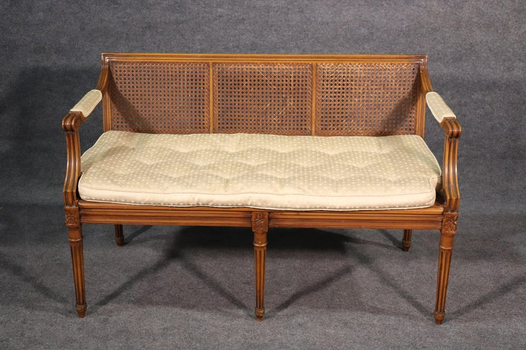 This is a beautifully simple Louis XVI settee with good cane surfaces and seating and a goose feather cushion, circa 1940. The settee shows no cane damage and is in good overall vintage condition.   The settee measures 29.5 tall x 46.5 wide x 22