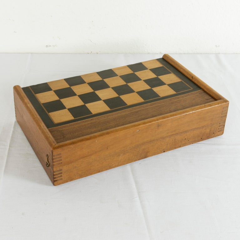 This French walnut marquetry folding game box from the turn of the 20th century is for both checkers and backgammon. It is finely constructed with dovetailed corners, inset hinges, and a locking brass hook on each side. The checker board side of the