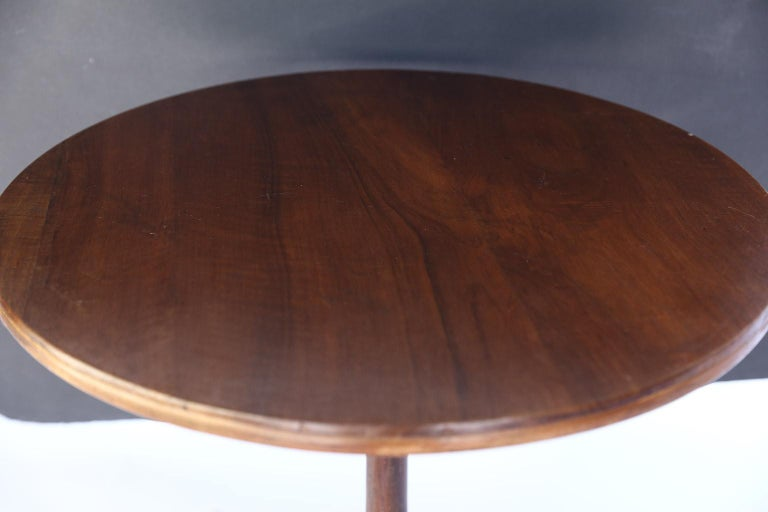 Made of walnut, this beautiful antique French pedestal table is perfect as an end or side table. The table features a round top poised on a pedestal with tripod legs, brass casters and a hand waxed finish.