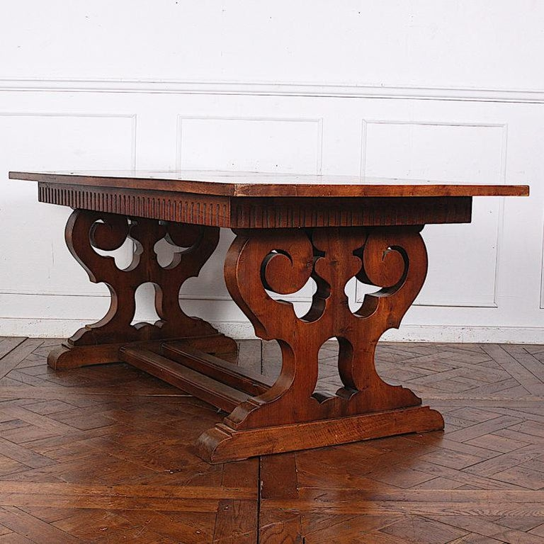 An early 20th century French parquet top walnut trestle table with dramatically-shaped end supports joined by a double stretcher.