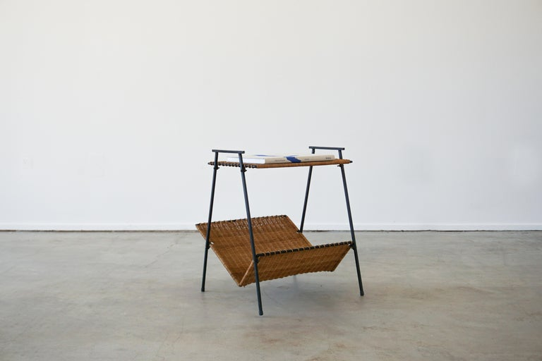 Great French wicker and iron table with lower magazine rack. Beautiful angled legs and functional design with whipped wicker edges.