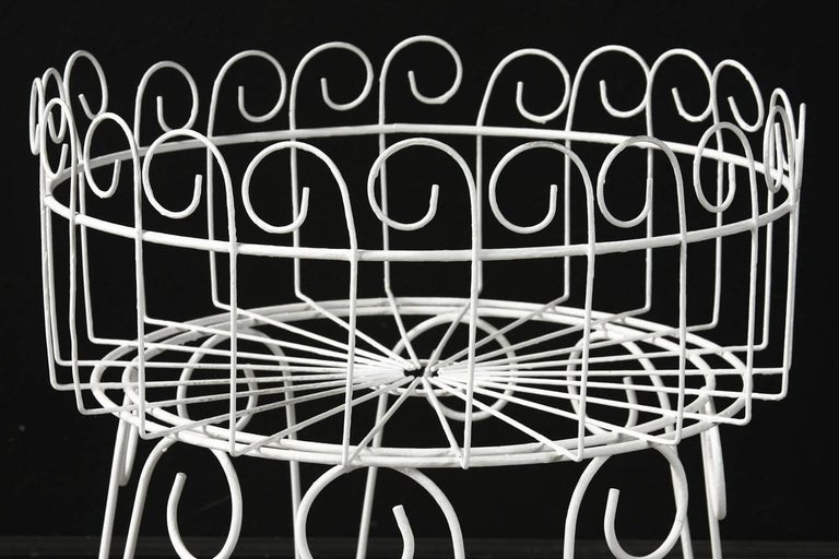Painted French wire basket plant stand or jardinière with hairpin legs. Features a decorative scrolled motif on top and could serve many purposes. Stable with a flat bottom and round ring stretcher conjoining the legs.