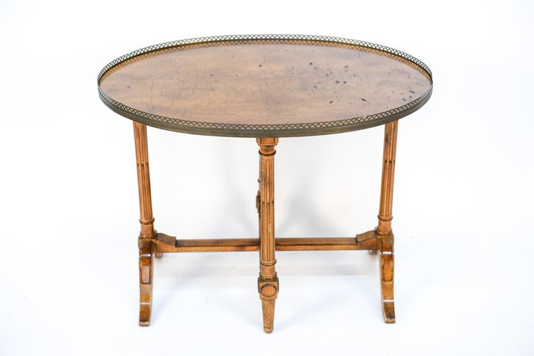 The stylish 19th century French table surrounded by a pierced brass gallery with elegantly carved trestled base legs with stretchers is the perfect size and height for an occasional tea table or distinct side or end table.