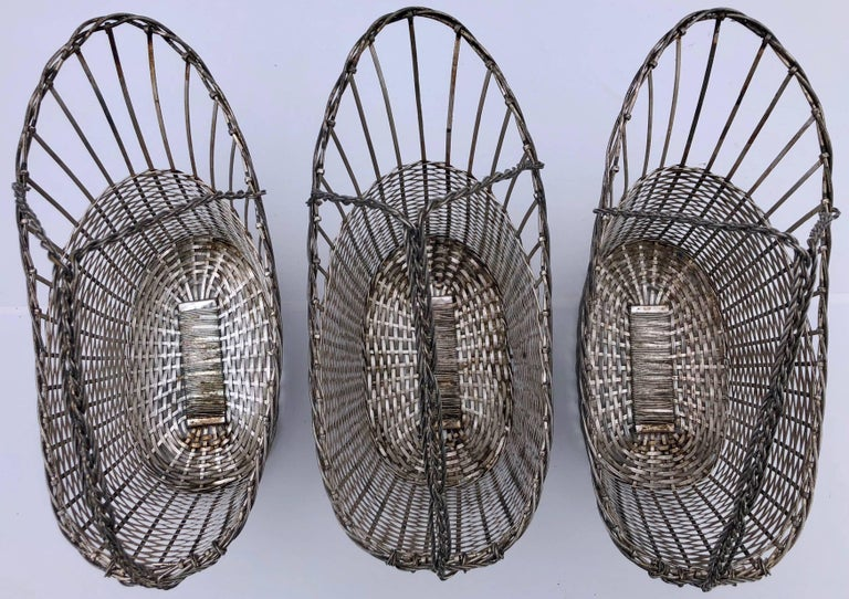 This set of three metal bottle baskets made of woven metal strips. They were used in a Parisian restaurant for decades and are very solid, yet very light, which is what one ideally needs when holding the basket in one hand to pour wine. A perfect