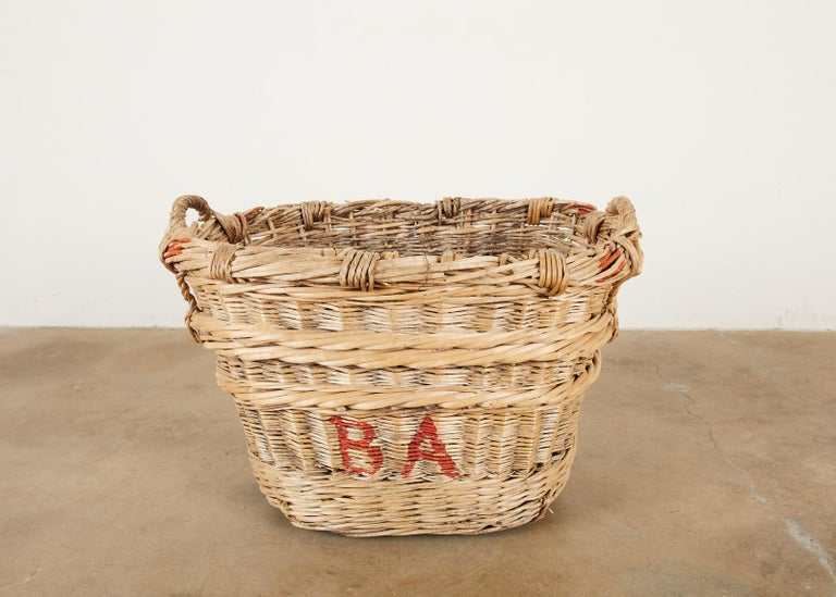 Rustic French chateau champagne grape harvesting basket constructed from woven wicker reeds. Features a thick braided top with handles on each end and brightly colored champagne house initials on the sides reading BA in vivid red paint. Reinforced