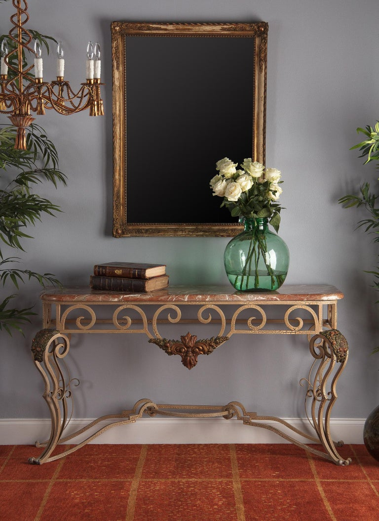 An elaborate vintage wrought iron and marble console, French, circa 1950. The ornate wrought iron base is loaded with scrollwork. Each of the four legs consists of two thick bowed scrolls accented by sets of slim inner scrolls, all joined by four
