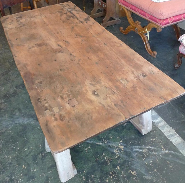 French 19th century stained pinewood coffee table top on two pinewood sawhorses.