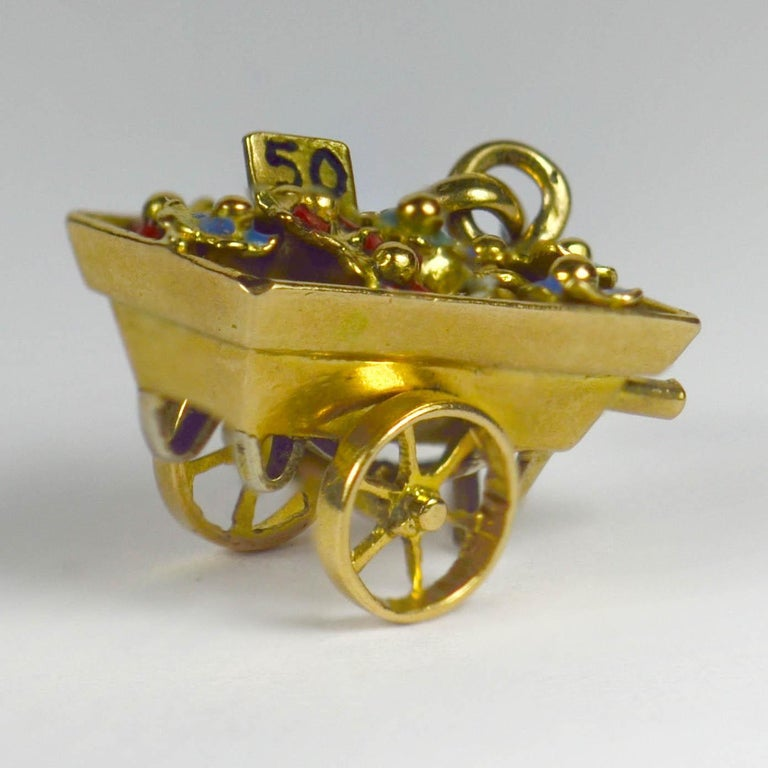 A French 18 karat yellow and white gold charm pendant designed as a flower sellers cart, each blossom coloured with enamel. Articulated with moving wheels. Stamped with the eagle's head for French manufacture of 18 karat gold.  Dimensions: 1.8 x 0.8