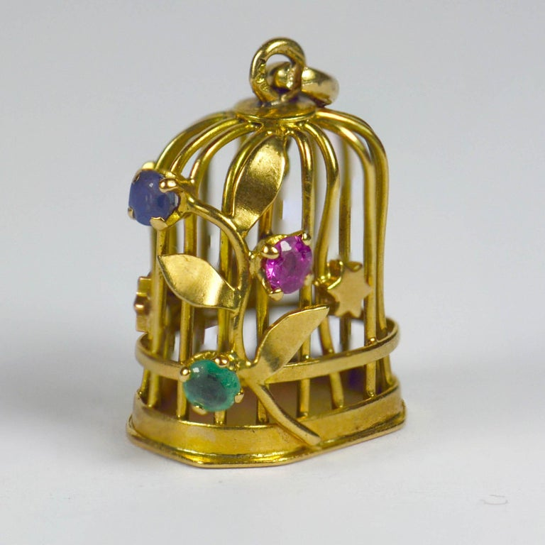 A French 18 karat yellow gold charm pendant designed as a bird cage with gem set flowering vine and stars, and a gold bird on a perch inside. Set with blue green and pink round cut paste, the charm is stamped with the eagle's head for 18 karat gold