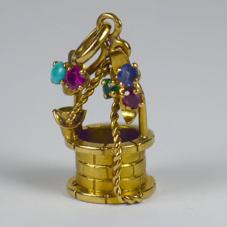 An 18 karat yellow gold French charm pendant designed as a wishing well with gem set flowering vines. Stamped with the eagle's head for French manufacture and 18 karat gold, with multi coloured round cut pastes representing flowers on the
