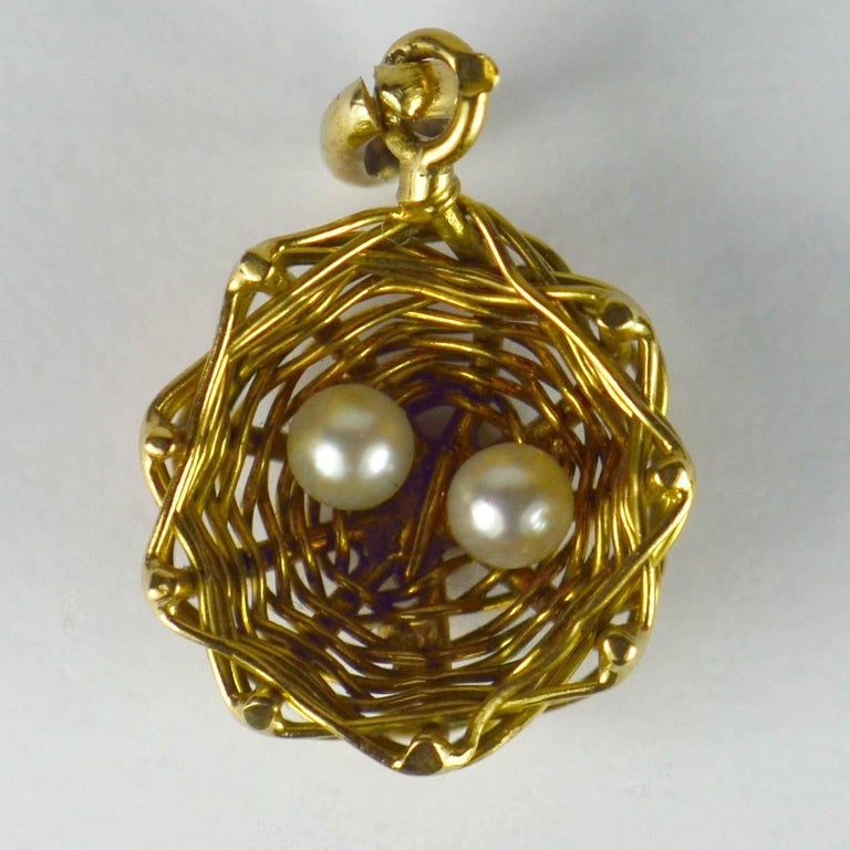 A French 18 karat yellow gold charm pendant designed as a bird nest with two white cultured pearl eggs inside. Stamped with the eagle's head for French manufacture and 18 karat gold.  Dimensions: 2 x 1.1 x 0.5 cm Weight: 1.34 grams