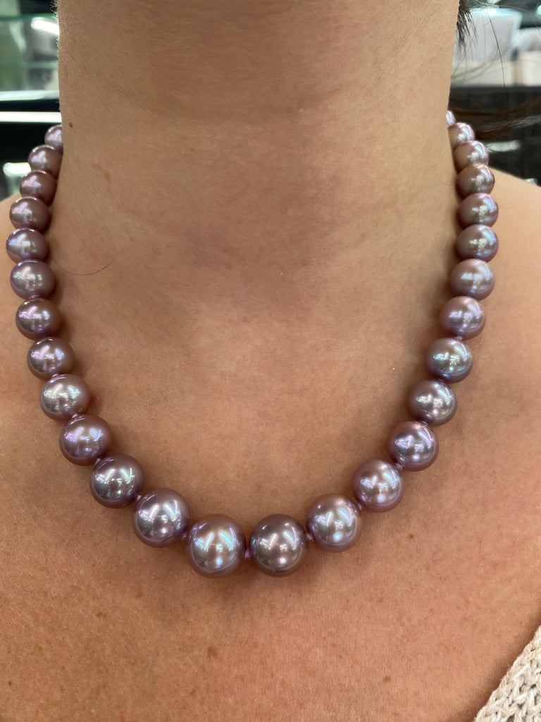 A lovely perfectly matched pearl strand necklace featuring 38 Freshwater Lavender Pearls measuring 10-13 mm with a high polish ball clasp in 14K White Gold.   Pearl quality: AAA Pearl Luster: AAA Excellent Nacre : Very Thick  Strand can be made to