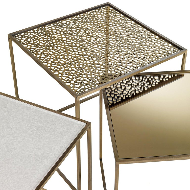 Part of the Friends collection of side tables, this piece will be an exquisite addition to a contemporary living room. Its square structure is made entirely of brass and comprises a base on three sides that supports a fretwork top. The irregular,